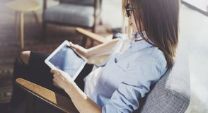 Young beautiful female student using touch pad at modern coworking place. Freelancer girl working on her digital tablet. stock image