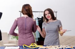 Young beautiful female tailor taking measurements. The young beautiful female tailor taking measurements royalty free stock image