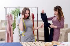 Young beautiful female tailor taking measurements. The young beautiful female tailor taking measurements stock photo