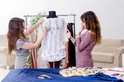 Young beautiful female tailor taking measurements. The young beautiful female tailor taking measurements royalty free stock images