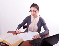 Young beautiful female teacher sitting at a table Royalty Free Stock Photos