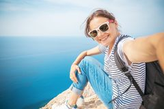 Young beautiful female tourist girl doing selfie on a blue sea b stock photos