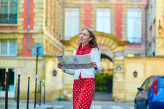 Young beautiful female tourist with map in Paris Royalty Free Stock Images