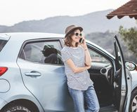 Young beautiful female travel girl in hat and sunglasses speaks royalty free stock photography