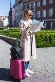 Young beautiful female traveler with suitcase lost in the city stock images