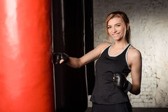 Young, beautiful and fit blond lady is working out in a gym decorated in loft style. Stock Photo