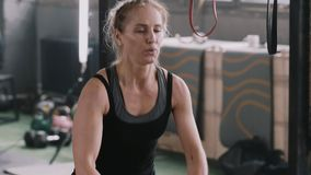 Young beautiful fit blonde woman exercising to the limit with battle ropes, taking a break to rest smiling in large gym. Motivation and following healthy stock video