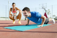 Young, beautiful, fit and healthy personal trainer counting push Royalty Free Stock Image