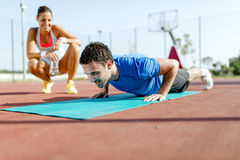 Young, beautiful, fit and healthy personal trainer counting push Stock Photos
