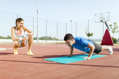 Young, beautiful, fit and healthy personal trainer counting push Royalty Free Stock Photography
