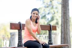 Young beautiful and fit sport woman talking happy with mobile phone smiling after running workout sitting on park bench relaxed Royalty Free Stock Photo