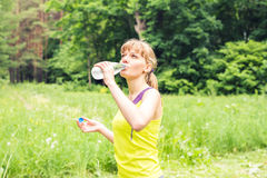 Young beautiful fit woman drink water after her exercise. Royalty Free Stock Photography