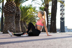 Young beautiful fit woman with perfect slender body enjoying rest after workout outdoor Stock Image