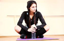 Young beautiful fit woman sitting on the yoga mat Stock Images