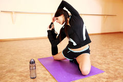 Young beautiful fit woman stretching on yoga mat Stock Photo