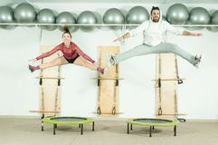 Young beautiful fitness couple workout extreme acrobatic exercise on trampoline jumps as preparation for the competition, selectiv Stock Images