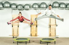 Young beautiful fitness couple workout extreme acrobatic exercise on trampoline jumps as preparation for the competition, selectiv stock photo