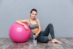 Young beautiful fitness girl with pink ball holding water bottle Stock Photo