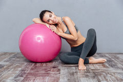 Young beautiful fitness girl with pink ball isolated on grey. Young beautiful smiling fitness girl with pink ball and looking at camera isolated on grey royalty free stock photography