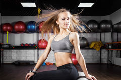 Young beautiful fitness girl sitting on red ball. Young beautiful fitness girl sitting on fitness ball in health club. Blonde sporty woman in the gym Stock Photo