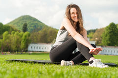 Young beautiful fitness woman doing pilates exercises in the par Stock Photography