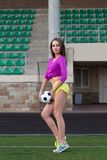 Young and beautiful fitness woman posing on playing field Royalty Free Stock Photo