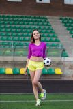 Young and beautiful fitness woman posing on playing field Royalty Free Stock Image