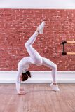 Young beautiful flexible girl in white jumpsuit is posing in a dance studio. Stretching and body ballet theme. Modern dance trend stock image