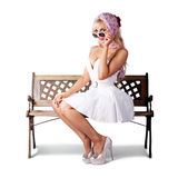 Elegant pinup lady sitting alone on park bench Royalty Free Stock Photos