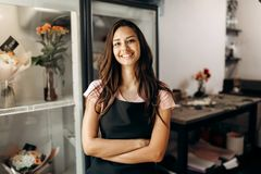 Young beautiful florist in a black apron stands and smiles in a flower shop stock photography