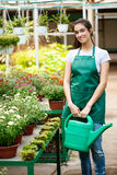 Young beautiful florist watering flowers over blury outdoor background. Stock Photos