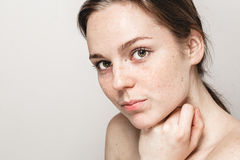 Young beautiful freckles woman face portrait with healthy skin. Studio shot Stock Photo