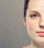 Young beautiful freckles woman half face portrait with healthy skin Royalty Free Stock Images
