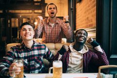 Victory. Group of young beautiful friends watching TV and cheering for their team while resting in pub. royalty free stock photography