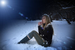 The young beautiful frozen woman sits in snow in the night park Royalty Free Stock Images