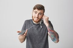 Young beautiful funny bearded tattooed caucasian man with ginger short hair in casual modern outfit looking in camera Stock Photography