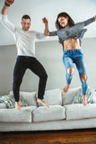 Young beautiful funny couple man woman in love having fun jumping from bed indoors at home royalty free stock images