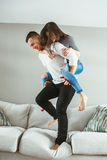 Young beautiful funny couple man woman in love having fun jumping from bed indoors at home. Portrait of young beautiful funny couple men women in love having fun royalty free stock image