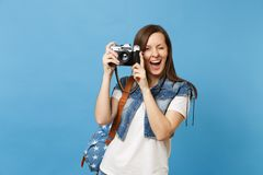 Young beautiful funny woman student in t-shirt, denim clothes with backpack blinking holding retro vintage photo camera. Isolated on blue background. Education stock photography