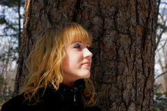 The young beautiful girl. In a wood stands near a tree Stock Image