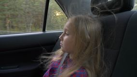 Young beautiful girl on adventure road trip inside car the wind in her hair. Pretty serious white girl. Road speed drive. Strong wind. Travel autumn sunset stock video footage