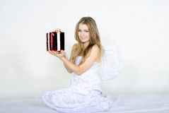 The young beautiful girl an angel with a gift. On a white background Royalty Free Stock Photo