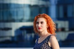 Young beautiful girl with beautiful appearance. Red-haired woman with a pretty face at sunset. A charming, smiling woman portrait Stock Photo