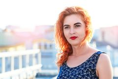 Young beautiful girl with beautiful appearance. Red-haired woman with a pretty face at sunset. A charming, smiling woman portrait Royalty Free Stock Photos