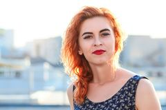 Young beautiful girl with beautiful appearance. Red-haired woman with a pretty face at sunset. A charming, smiling woman portrait Royalty Free Stock Image