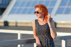 Young beautiful girl with beautiful appearance. Red-haired woman with a pretty face at sunset. A charming, smiling woman portrait Stock Photos
