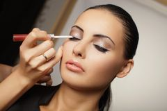 Young beautiful girl applying make-up Stock Photography