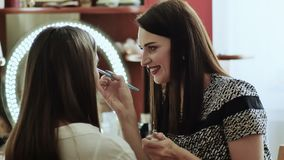 Young beautiful girl applying make-up by make-up artist stock footage