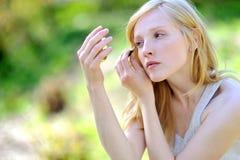 Young beautiful girl applying make-up outdoor Royalty Free Stock Photos