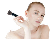 Young beautiful girl applying makeup by brush. royalty free stock images